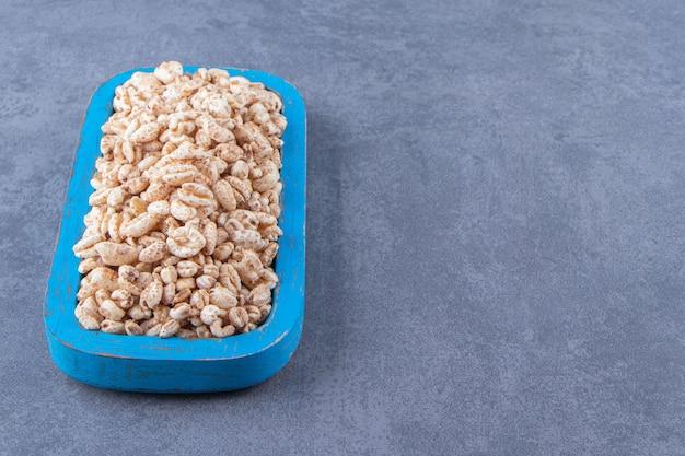 大理石のテーブルの上に、木の板に甘いコーンフレーク。