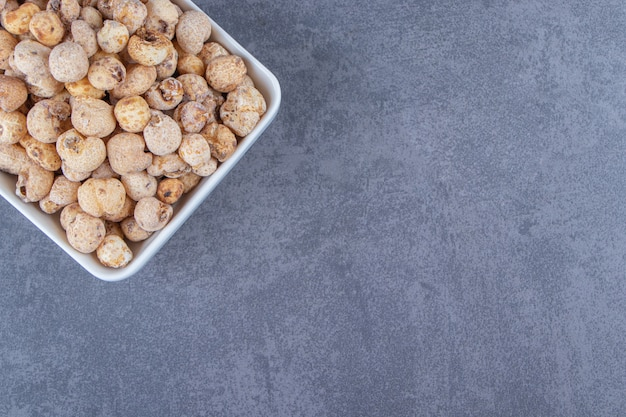 Сладкие кукурузные хлопья с мюсли в миске на мраморном фоне. фото высокого качества