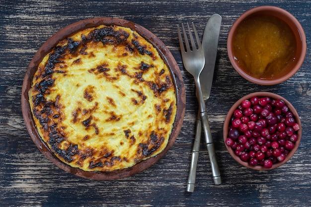 나무 테이블에 건포도와 양질의 거친 밀가루를 넣은 달콤한 코티지 치즈 캐서롤. 구운 코티지 치즈 캐서롤이 있는 세라믹 그릇, 클로즈업, 위쪽 전망