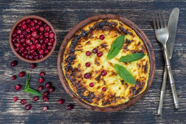 木製のテーブルにレーズンとセモリナ粉を添えた甘いカッテージチーズのキャセロール。焼きカッテージチーズのキャセロールとセラミックボウル、クローズアップ、上面図