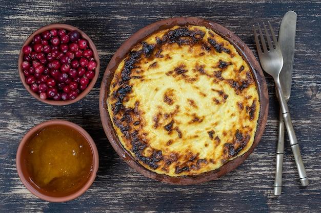 木製のテーブルにレーズンとセモリナ粉を添えた甘いカッテージチーズのキャセロール焼きカッテージチーズのキャセロールを添えたセラミックボウルの上面図を閉じる