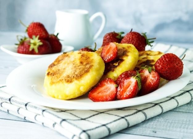 접시에 있는 달콤한 코티지 치즈 팬케이크는 딸기 러시아 시르니키 리코타 튀김 또는 두부 튀김을 제공합니다.