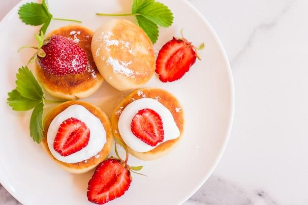접시에 달콤한 코티지 치즈 팬케이크는 딸기와 함께 제공됩니다. 러시아어 syrniki, 리코타 튀김 또는 두부 튀김.