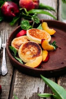 プレートのクローズアップでラズベリーブラックベリーとスグリと甘いカッテージチーズのパンケーキ