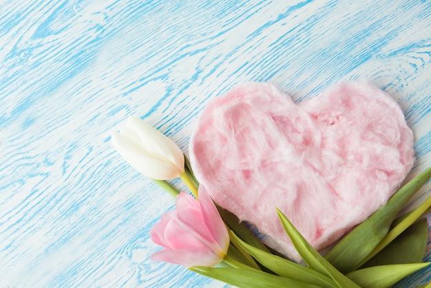 青い木製の背景にハート型の甘い綿菓子と繊細なピンクのチューリップ。コピースペース