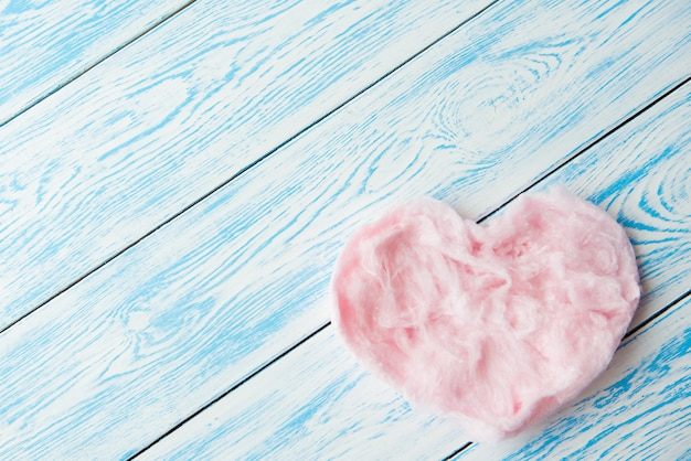 Sweet cotton candy in heart shape on blue wooden table. copy space