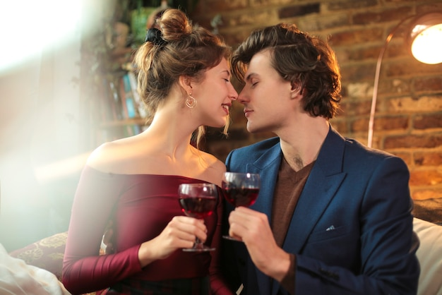 Sweet couple celebrating with a glass of red wine, at home