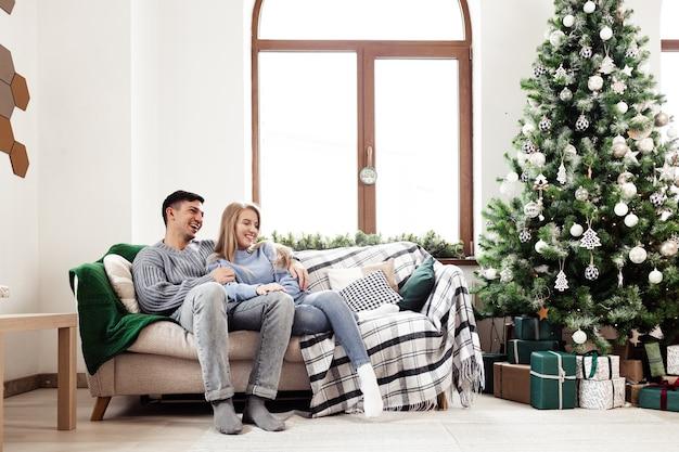 Сладкая парочка обнимается на диване у себя дома во время рождества