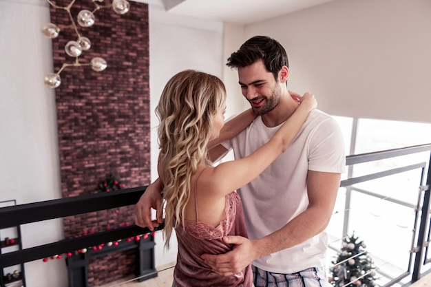 甘いカップル。彼のスリムな金髪の長い髪の妻を抱きしめながら幸せそうに見える白いtシャツのハンサムなひげを生やしたブルネットの男
