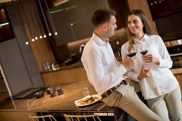 고급 부엌에서 낭만적 인 저녁 식사 후 레드 와인을 마시는 데 달콤한 커플