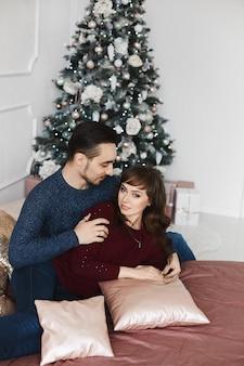 Сладкая парочка обнимает друг друга на кровати в спальне, украшенной на рождество