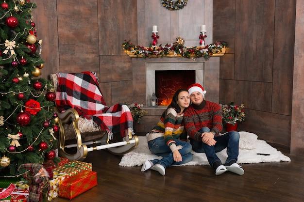 装飾された暖炉の前とプレゼントとクリスマスツリーの近くの敷物の上に座っている暖かいセーターの甘いカップル