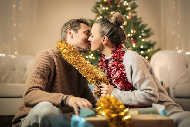 Sweet couple kissing, while preparing christmas decorations