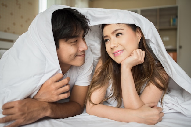 Sweet couple playing under the blanket on the bed