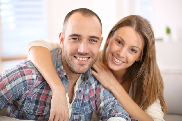 Sweet couple sitting in sofa at home