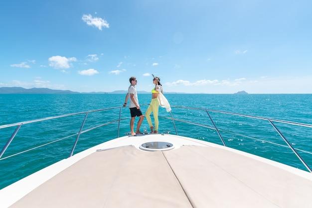 Sweet couple standing on edge of luxury yacht.