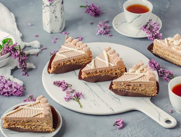 テーブルの上の紅茶と甘いクリームケーキ
