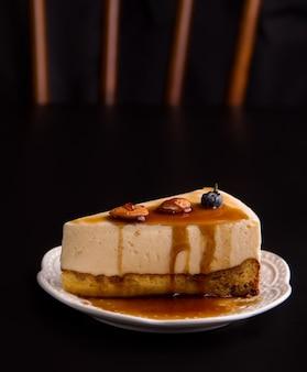 검은 배경에 카라멜과 견과류를 넣은 달콤한 크림 치즈 케이크 디저트. 복사 공간