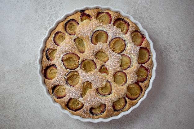 Сладкий сливочный торт со свежими плодами сливы в белой форме для выпечки с сахарной пудрой на светло-серой поверхности