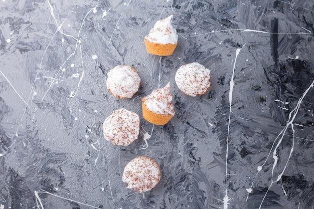 대리석 배경에 흩어져있는 달콤한 크림 미니 컵 케이크.