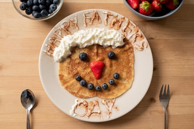 幸せな父の日の碑文、パパのためのギフトと変な顔の形をしたホイップクリームとベリーで飾られた甘いクレープ