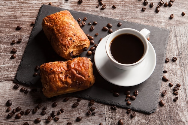 Sweet croissants with almonds, hot coffee and spreaded coffee beans. sweet breakfast