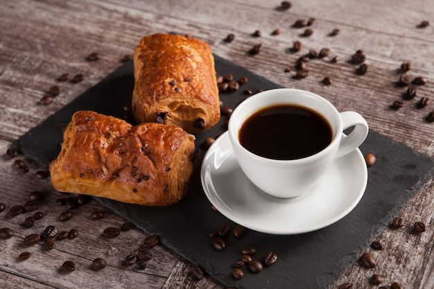 Sweet croissants with almonds, hot coffee and spreaded coffee beans. sweet breakfast.