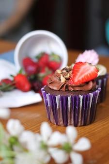 딸기와 꽃 나무 테이블에 달콤한 컵 케이크