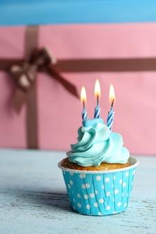 Сладкий кекс со свечой на синем деревянном столе против розовых подарочных коробок