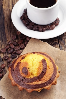 Sweet cupcake with chocolate and cup of coffee closeup