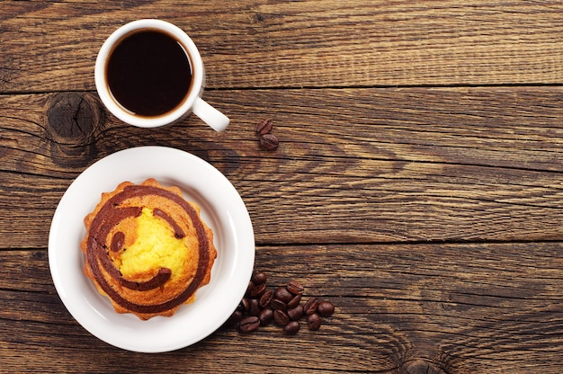 Sweet cupcake with chocolate and cup of coffee on wooden table. top view