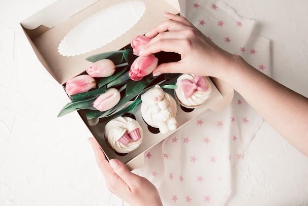 Сладкие капкейки и розовые цветы в коробке женскими руками