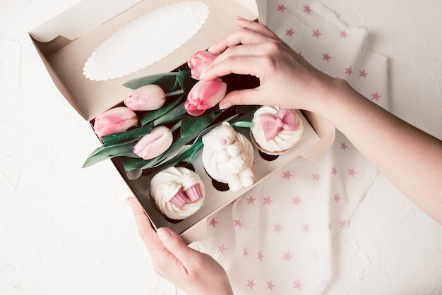 Sweet cupcakes and pink flowers in a box with women's hands