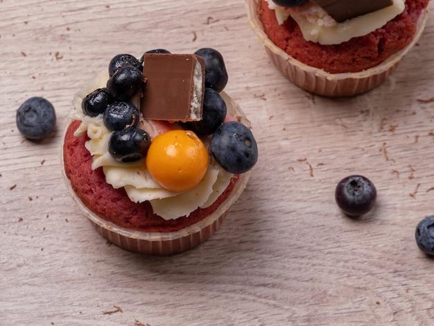 ブルーベリー、クリームムース、チョコレートの甘いカップケーキ。おいしい自家製ケーキ。