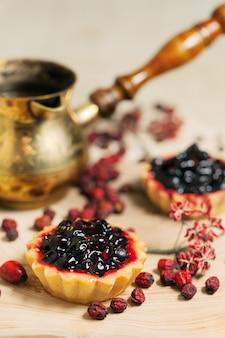 테이블에 신선한 유기농 딸기와 달콤한 컵 케이크
