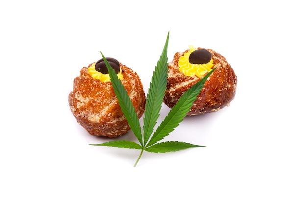 白い背景で隔離のマリファナの葉と甘いカップケーキ。