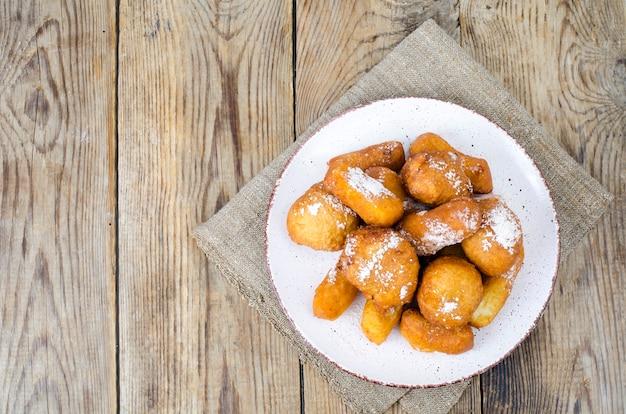 Сладкие булочки пончиков творога с сахарной пудрой на деревянном столе.