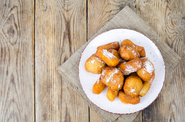 Sweet curd donuts buns with powdered sugar on wooden table.