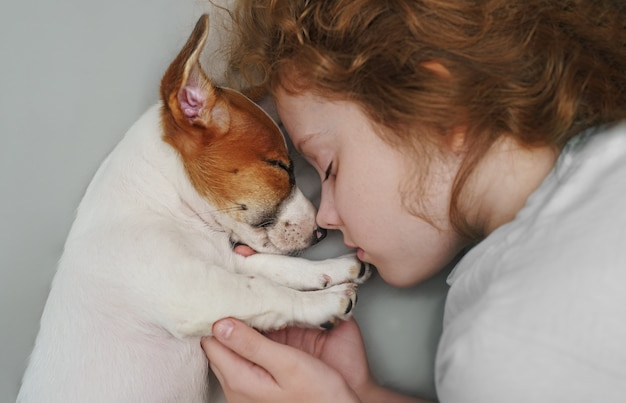Sweet curly girl and puppy jack russell dog is sleeping in night.