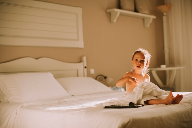 Sweet curly little girl with a towel over her wet body siting in a bedroom after shower