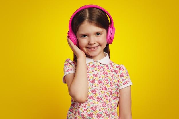Милая милая девушка в стильной летней одежде слушает музыку в наушниках