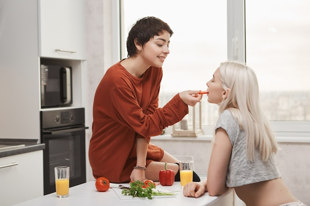 Sweet and cute indoor shot of hot shirt-haired woman feeding her girlfriend while sitting at kitchen table and preparing breakfast. foreplay of young sensual couple of girls