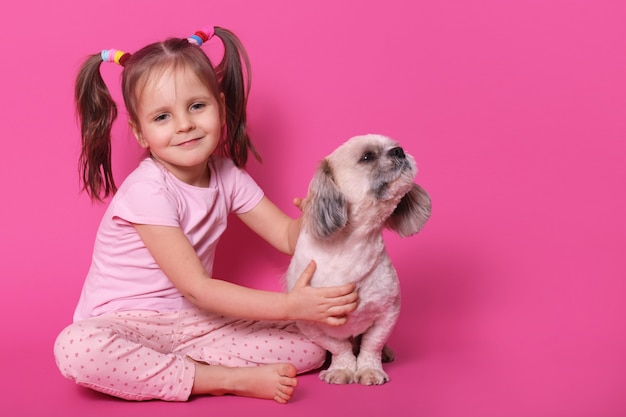 Sweet cute little child with two funny pony tails, being in good mood, spending free time with pet, holding it close, puppy looking aside, smelling, sitting calm. copyspace for advertisement.