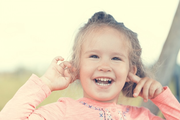 Sweet cute little girl outdoors with opened mouth outdoors portrait.