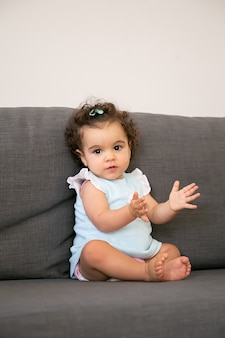 Sweet dark curly haired baby girl in pale blue cloth sitting on grey couch at home, a and clapping hands. kid at home and childhood concept