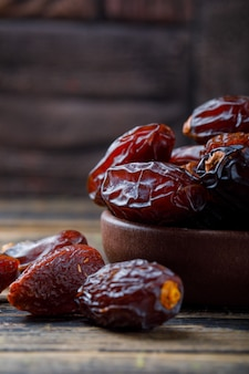 Sweet dates in a clay plate on stone tile and wooden background, close-up.