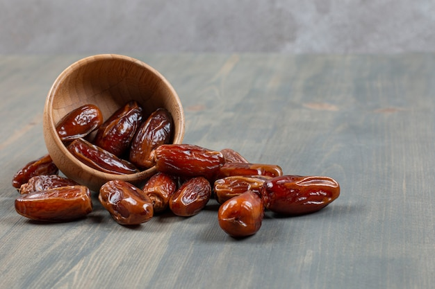 Sweet dates out of wooden bowl on marble surface