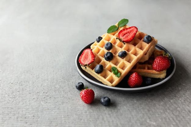 Сладкий вкусный завтрак с тарелкой вафель, клубники и черники, лист мяты на конкретном сером фоне. фото высокого качества