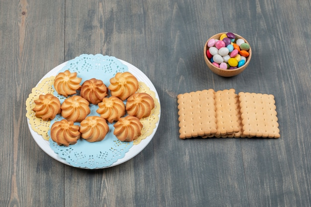 Сладкое вкусное подрумяненное песочное печенье в белой тарелке