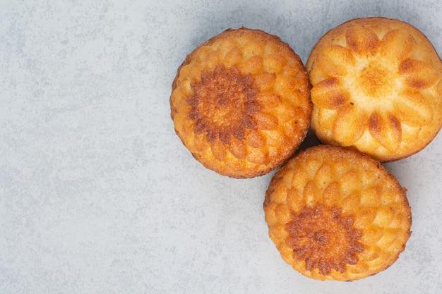 Сладкие вкусные кексы на белом столе.